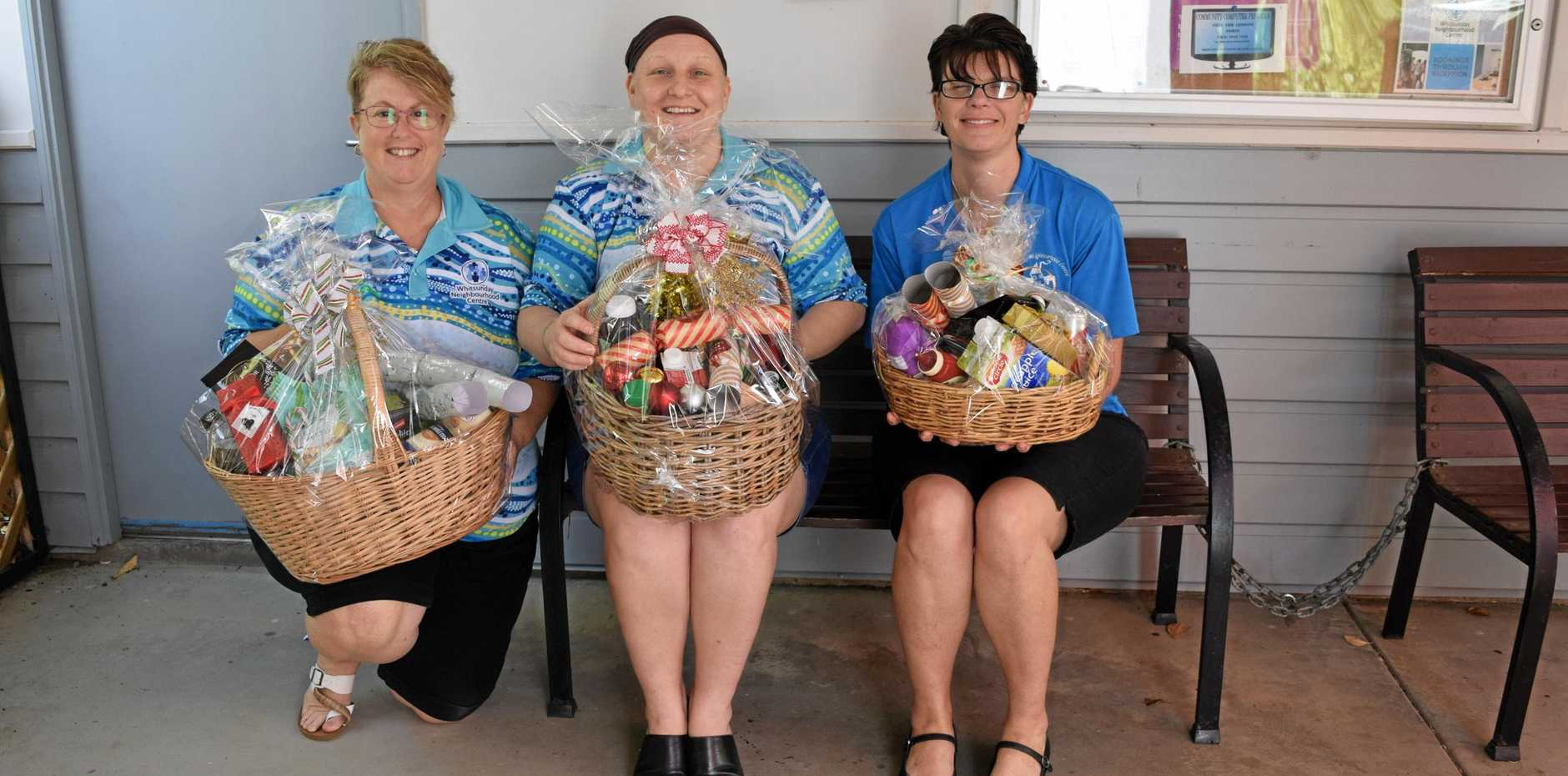 CHRISTMAS CHEER: Nikki Twohill, Rebecca Woods and Kerri Brown with Adopt-a-Family hampers.