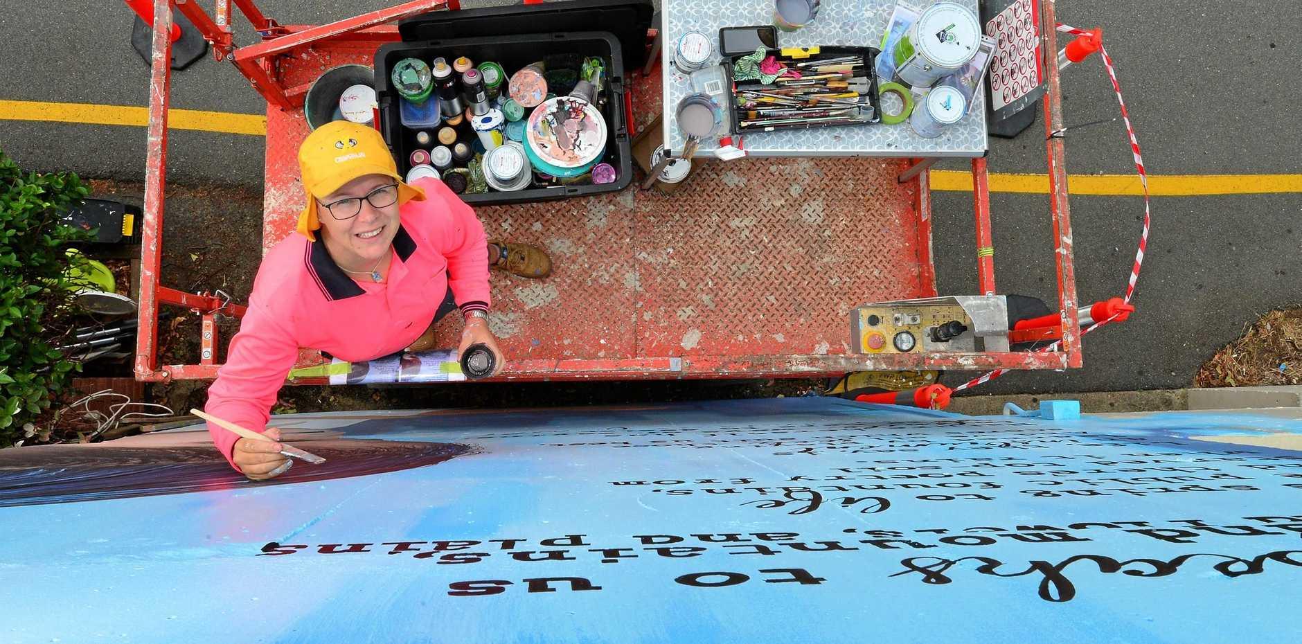 Mieke van den Berg puts her creative touch to a mural in Lamkin Lane in Caloundra.