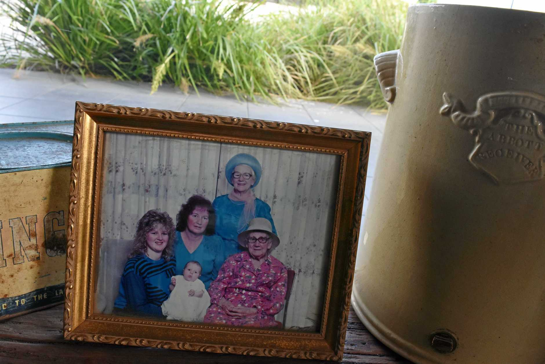 A photograph of Sharla Watson (the baby) and four generations of her family on display at the Farmer and Sun Cafe.