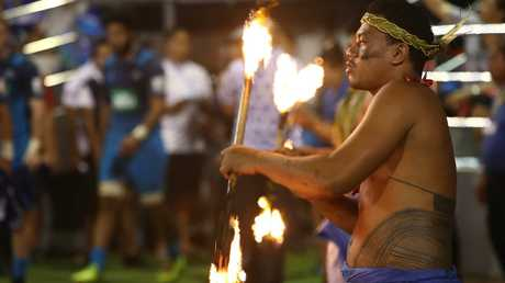 A fire dancer performs before a Super Rugby match between the Blues and Reds in Apia.