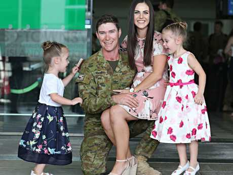 Returning soldier Ben Evans is greeted at Brisbane International Airport by daughters Mila 4 and Poppy 3 and partner Sam. Picture: Annette Dew