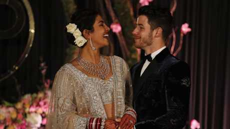 Bollywood actress Priyanka Chopra and musician Nick Jonas stand for photographs at their wedding reception in New Delhi, India. Picture: AP Photo/Altaf Qadri