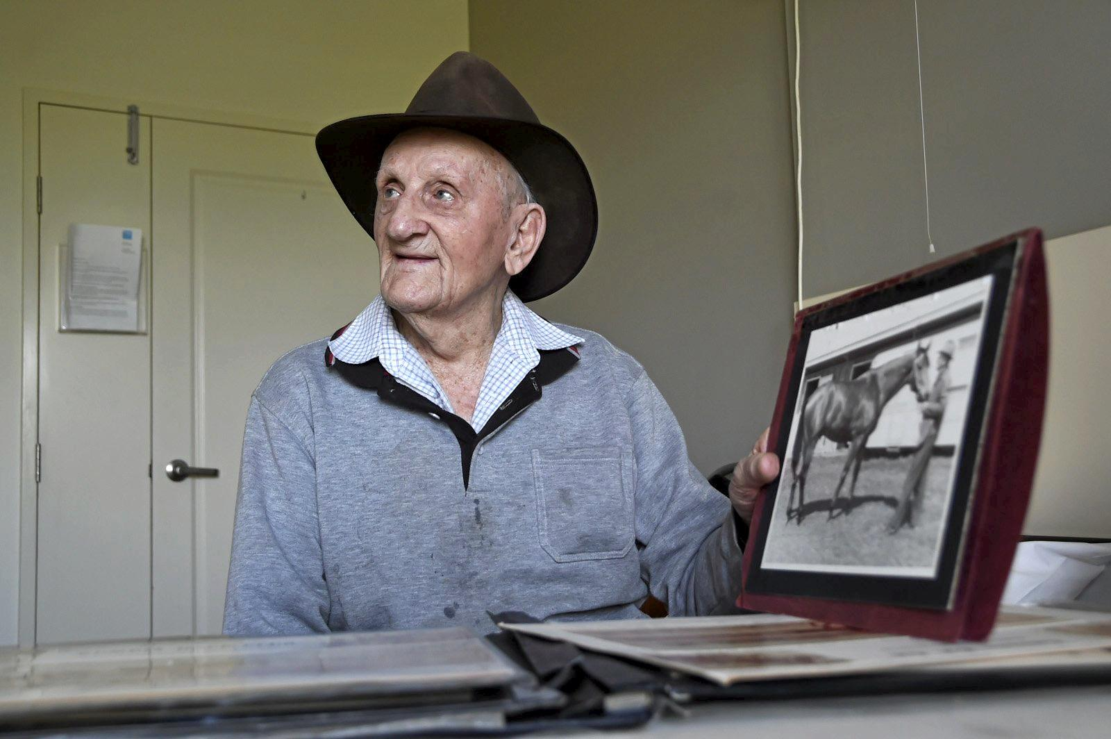 Former Toowoomba horse trainer and farrier Vince Nugent looking back this week at some of his racing memorabilia including a photo of himself with Dream Court.