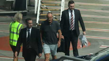 Chris Dawson (centre) is escorted by NSW Police detectives, including Daniel Poole (right) off a Qantas flight as he is extradited from the Gold Coast following his arrest. Picture: Dean Lewins/AAP