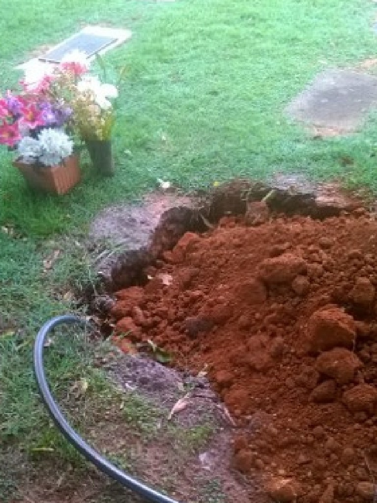 A picture of a hose going into a grave at Mt Gravatt. Picture: Greg Reidy.