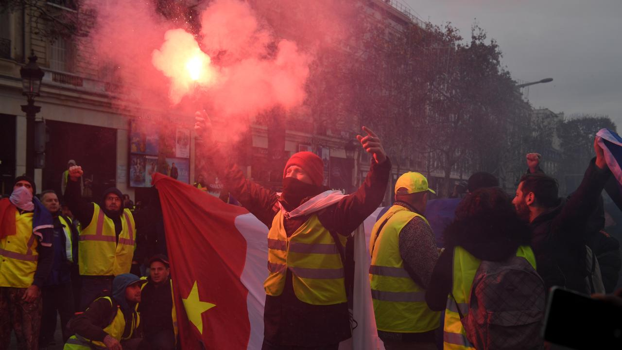 People light flares as they take part in the demonstration of the yellow vests near Champs-Elysees avenue. Picture: Getty