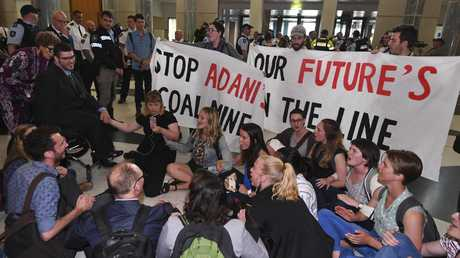 Greens Senator Jordan Steele-John (left) is seen with students and activists during a sit-in protest in the marble foyer at Parliament House. Picture: Lukas Coch/AAP
