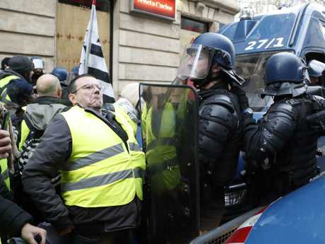 Police officers block demonstrators wearing yellow vests from entering a street in Paris. Picture: AP
