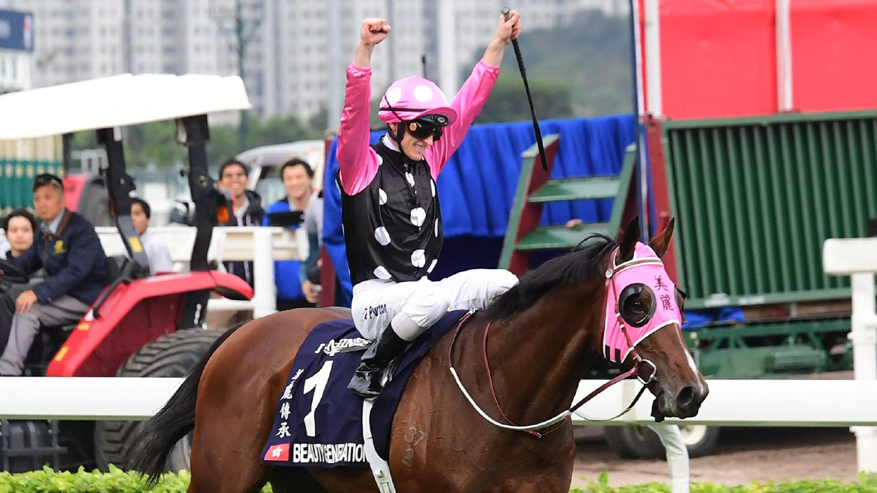 Zac Purton raises his arms in celebration after winning the Hong Kong Mile on Beauty Generation. Picture: Grant Peters/Trackside Photography