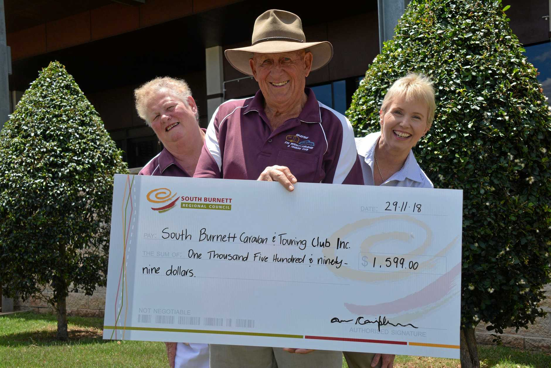 LIFE-SAVER: South Burnett Caravan and Touring Club secretary Liz Scott and President Wayne Coulson are presented with the defibrillator donation by South Burnett Regional councillor Roz Frohloff.