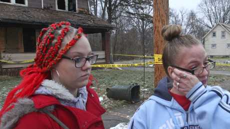 Two women wipe away tears at the scene of a deadly house fire in Youngstown, Ohio. Picture: William D. Lewis/The Vindicator