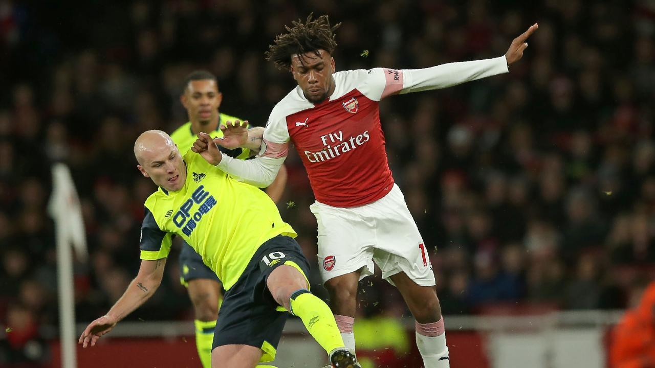 Arsenal's Nigerian striker Alex Iwobi (R) vies with Huddersfield Town's Australian midfielder Aaron Mooy (L)