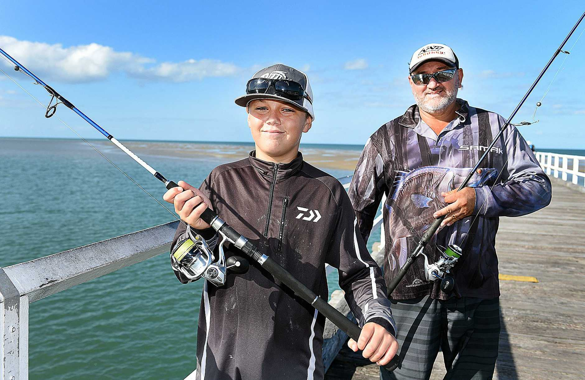 HOOKED: 12-year-old Addie Priala with his father, Addie, on Urangan Pier where he reeled in a large flathead on his new rod and reel.