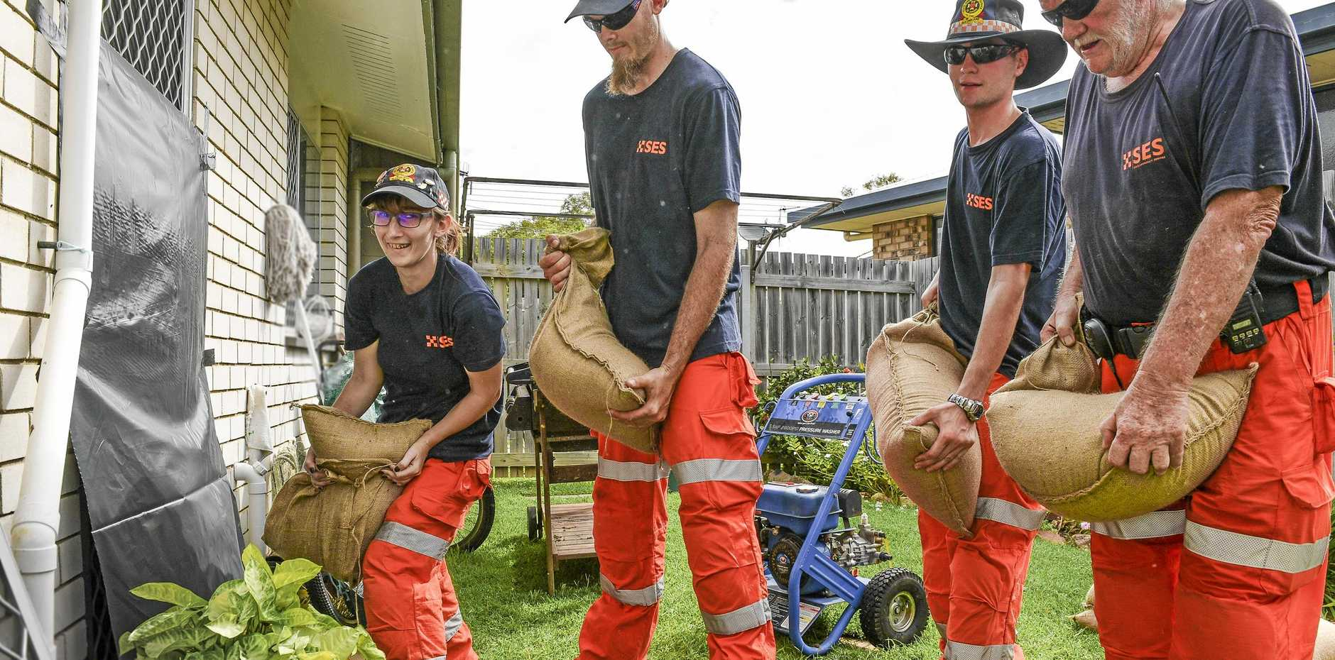 STILL GIVIVG: Gladstone and Mt Larcom SES volunteers Imogen Bangall, Jessie Bell, Daniel Batkines and Brian Kessner protect a property in South Gladstone by adding plastic and sandbags to the rear door.