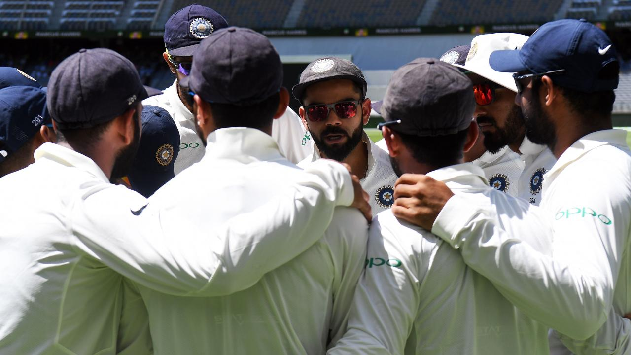 India's cricket captain Virat Kohli talks to teammates.