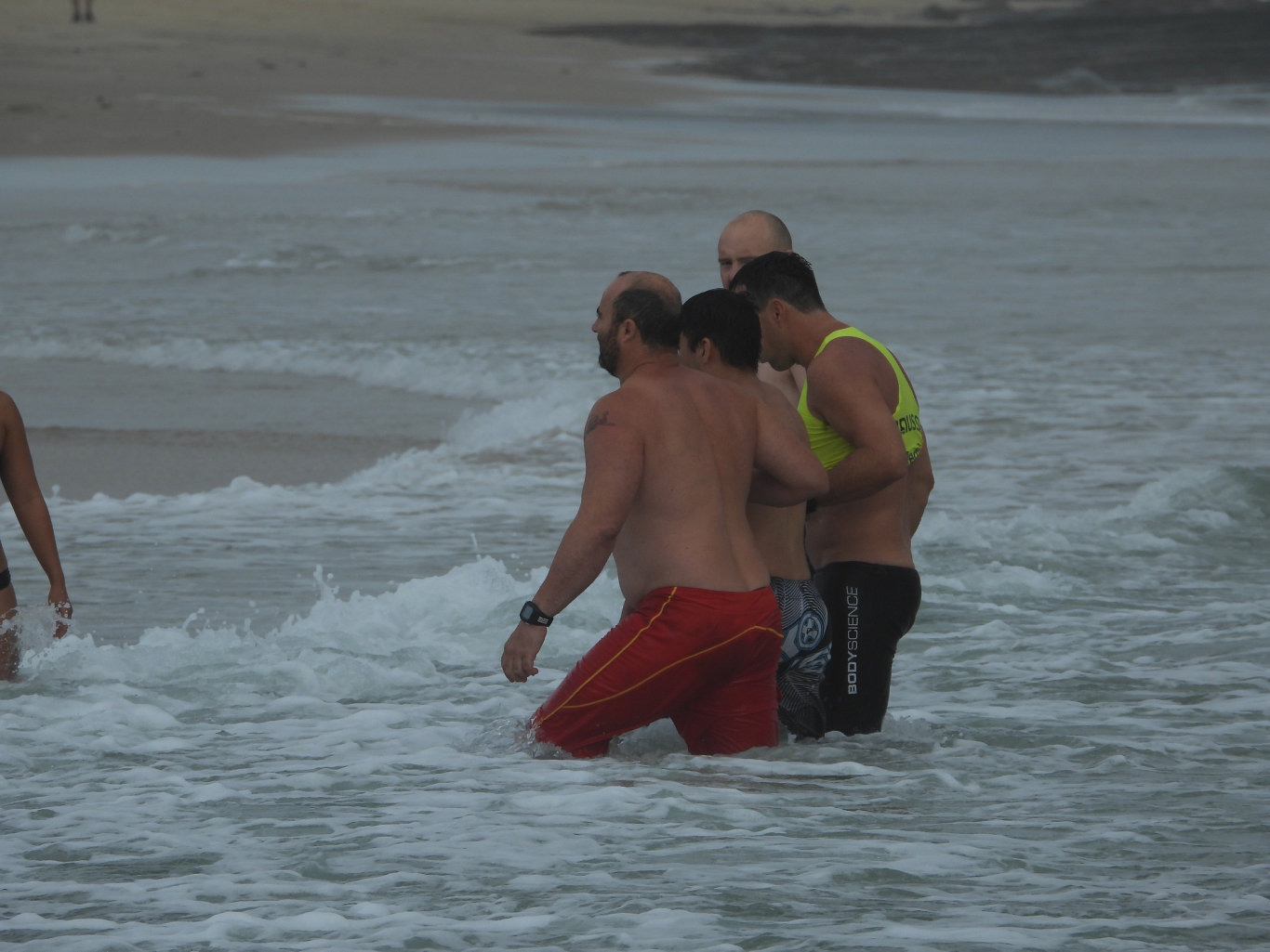 The tourist is helped to the shore at Mooloolaba before the start of patrols on Saturday morning.
