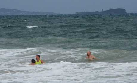 RESCUE DRAMA: A visitor is rescued at Mooloolaba while his friend watches on.