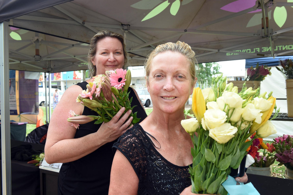 Urangan Pier Markets - Donna West and Julie Vojkovic from Sydney take a moment to smell the flowers.