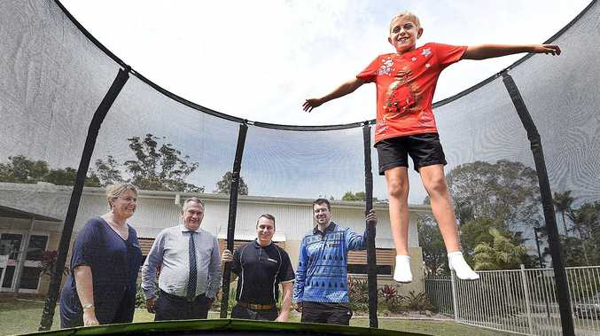 Hervey Bay Special School student Ryan Death on one of the school's trampolines - (L) Karen Folley (Acting Princ), Brett Hanwright (Fraser Coast Chronicle g/mgr.), Jordan Philp (Chronicle Editor) and Dale Paxton (owner Sportfirst). Alistair Brightman
