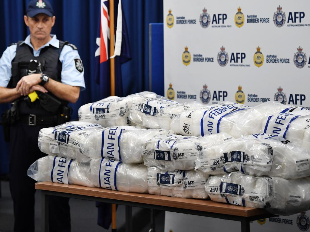 An AFP officer looks on as bags of crystal methamphetamine are seen on a table. Picture: David Moir