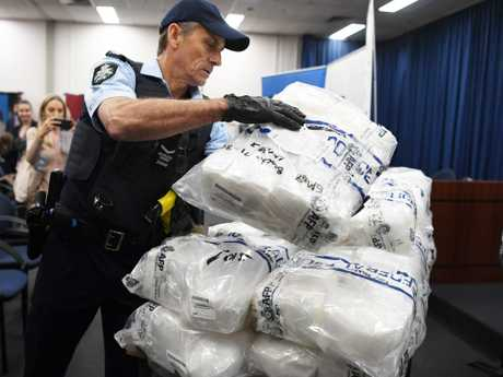 An Australian Federal Police officer places a bag of crystal methamphetamine on a table before a press conference at the AFP headquarters. Picture: David Moir
