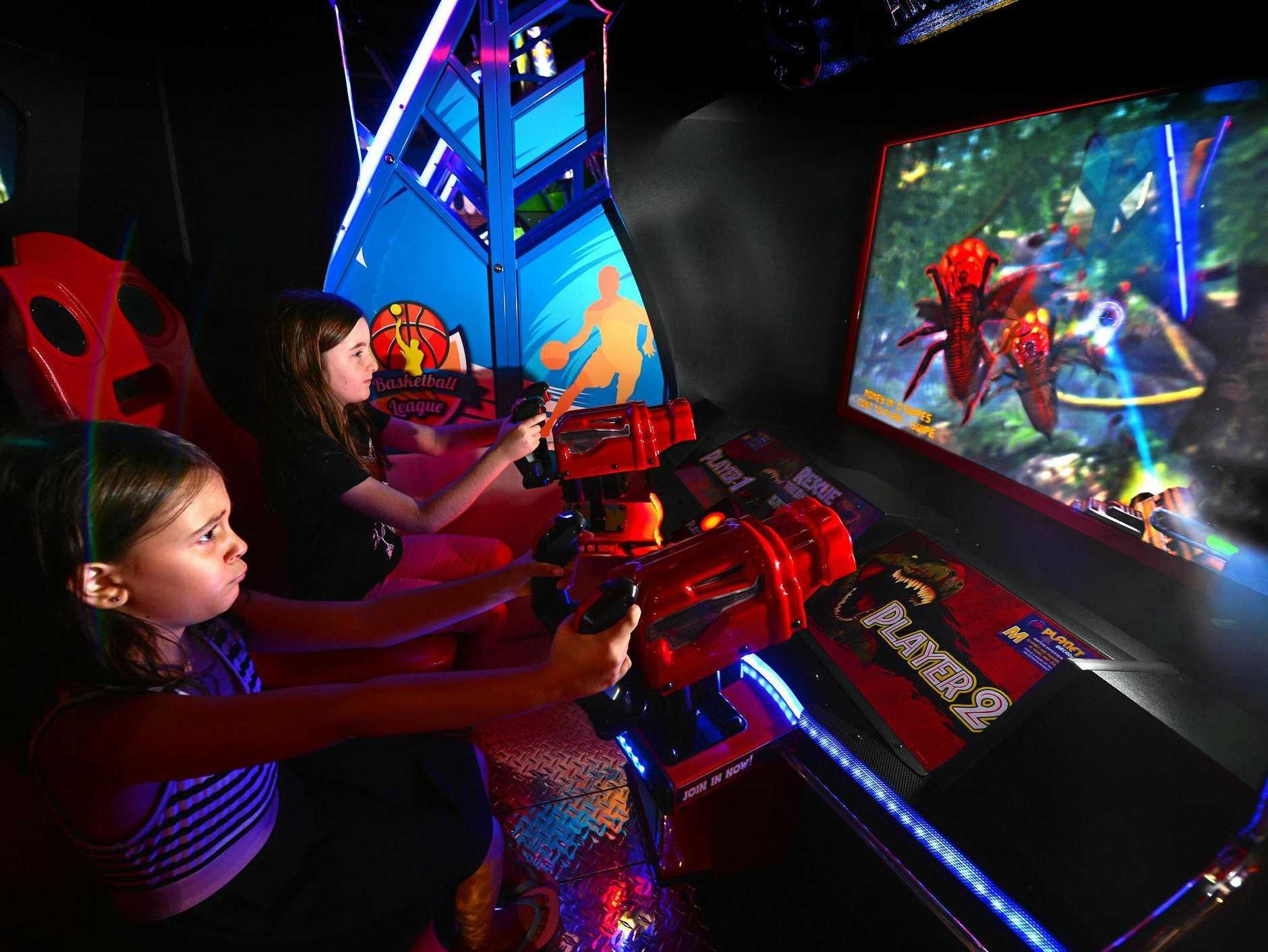 TAKING AIM: Nina Jensen, 7, and Rilee Woods, 9, unload some holiday boredom at Kawana Shoppingworld's new Planet Aracdes.