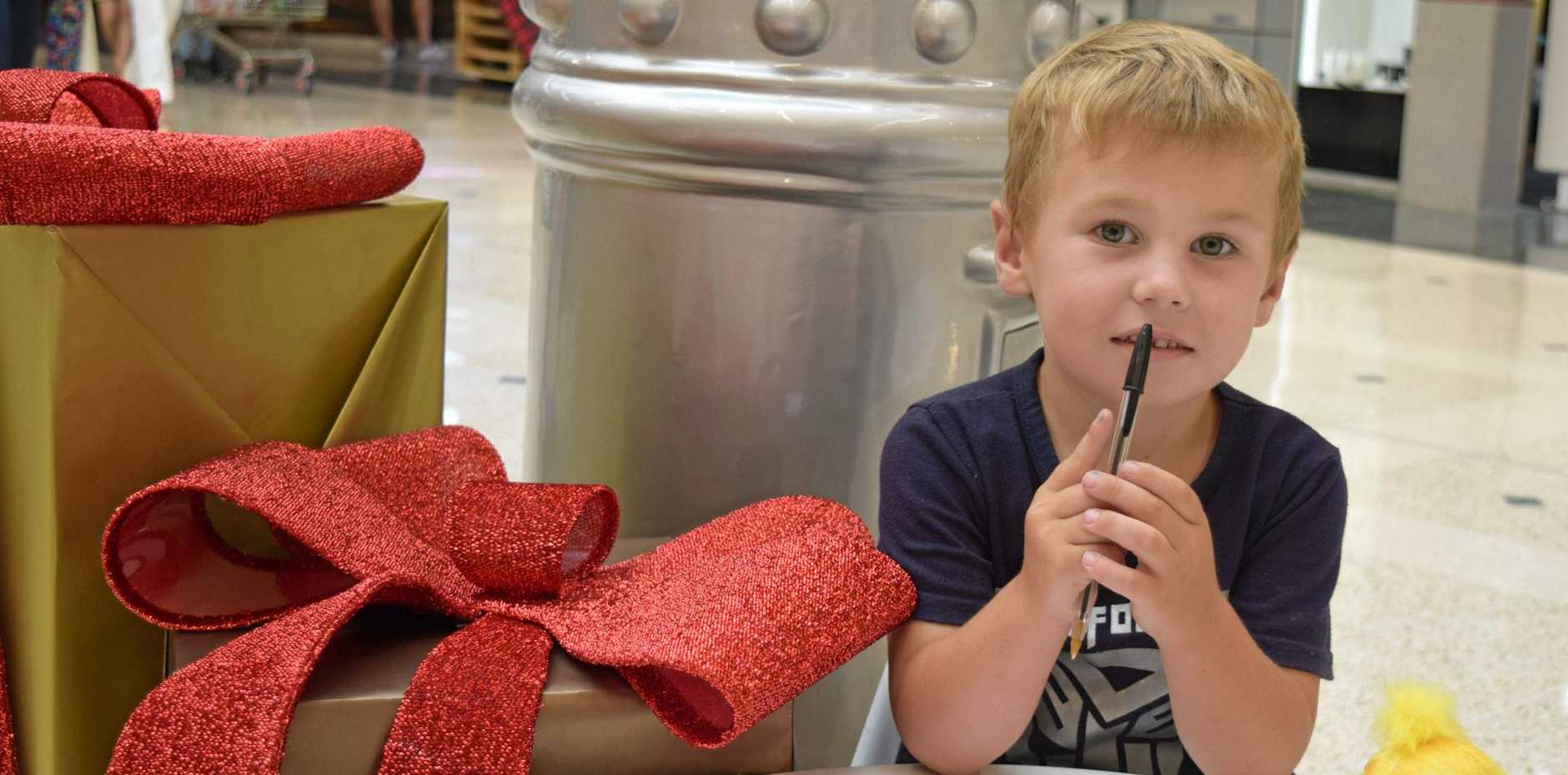 DEAR SANTA: Jacobee Windschuttel writing a letter to Santa and checking it twice, at Rose City Shoppingworld