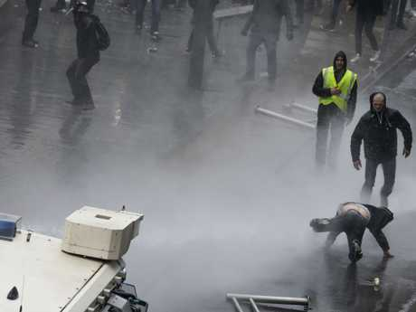 A protester is hit by a police water cannon during an anti-migrant demonstration outside of EU headquarters in Brussels. Picture: AP