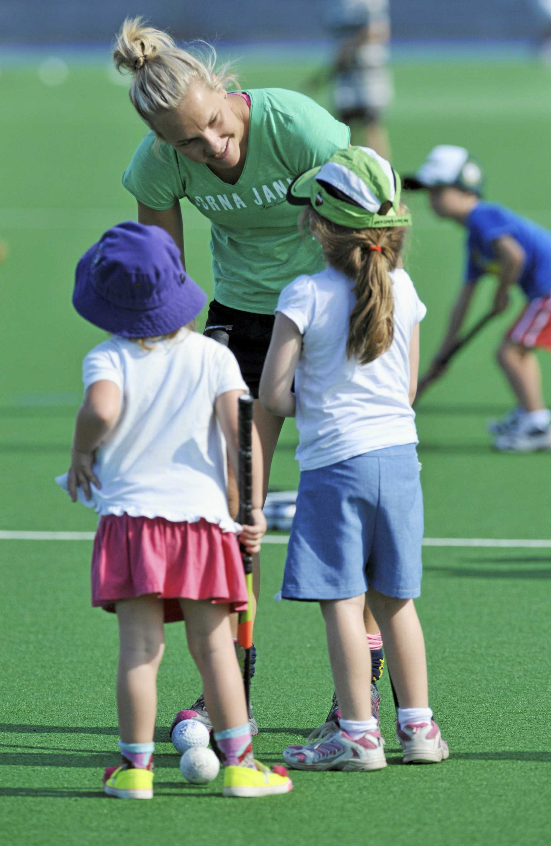 Kids gets their hockey sticks out and have a go at the Ipswich Hockey open day. Amy Korner gives some youngsters some advice. Photo: Rob Williams / The Queensland Times
