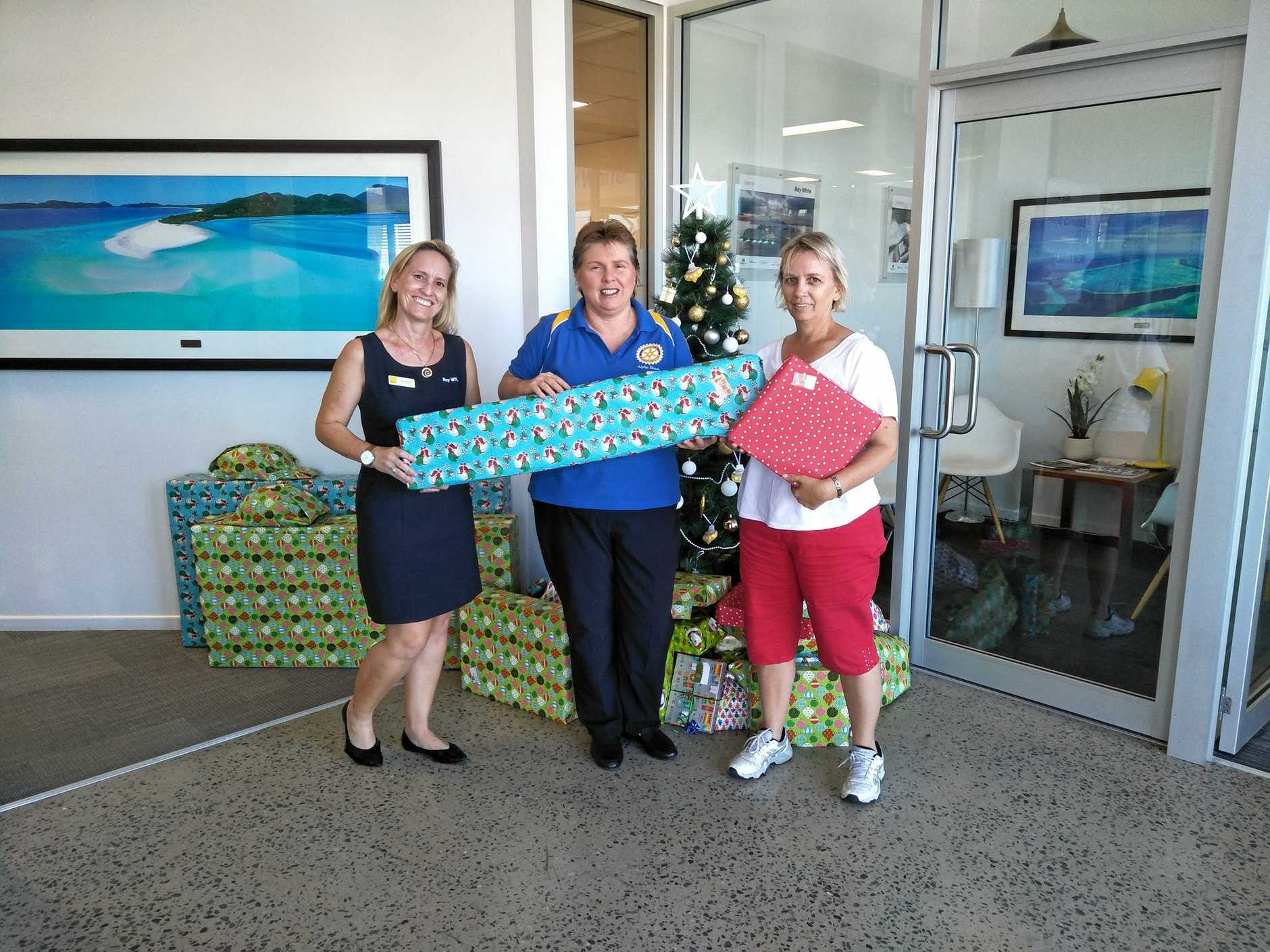 Ray White Whitsunday office manager Zoe Skinner, Rotary Club's Denise Norder and The Salvation Army's Donna Fraser round up gifts for community Christmas donations.