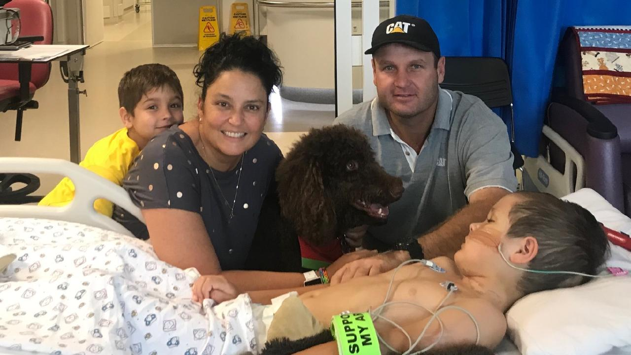 Eight-year-old Tablelands boy Joey Donald is proving to be a fighter. He is pictured at Townsville Hospital with his family by his side — brother Billy, mother Sarah, Jackson the Assistance Dog, and father Michael.