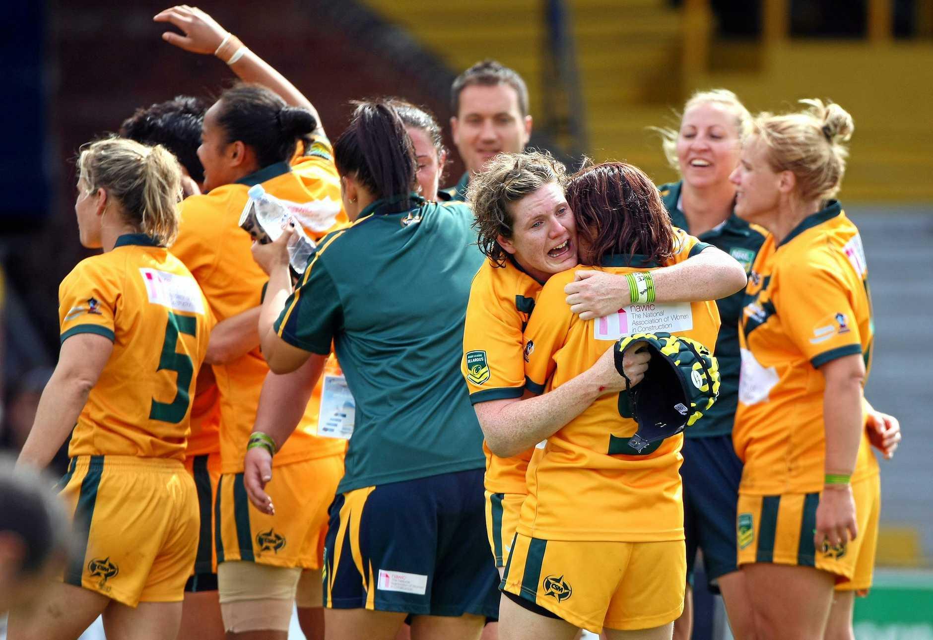 WINNERS: Jo Barrett (holding headgear) and Australian Jillaroos teammates celebrate a World Cup victory in England.