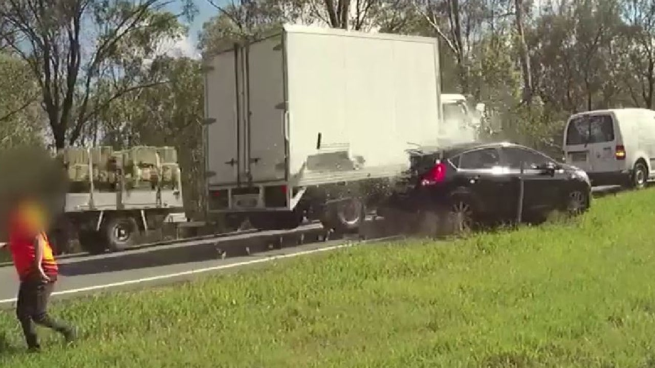 Police body camera vision showing a truck smashing into a parked car on the Warrego Highway.