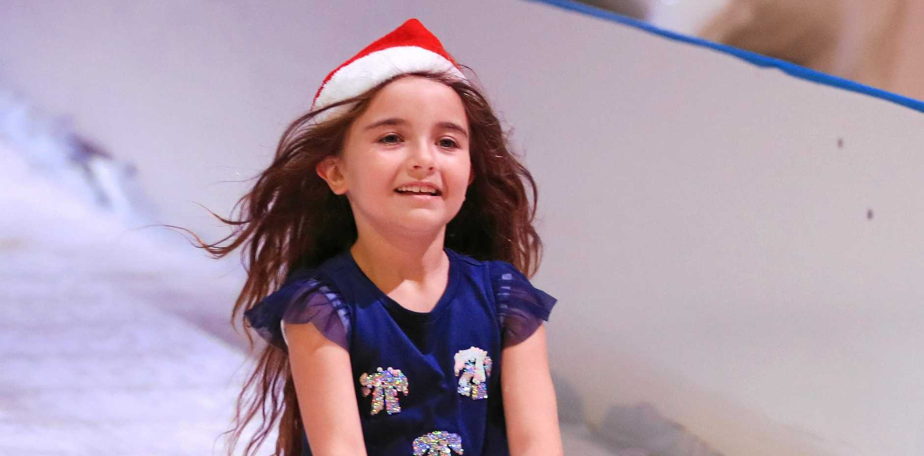 Enjoying the fun at Tweed Seagulls pop up indoor Ice Rink and White Christmas play ground ; Malina (7) takes off on the ice run toboggan.