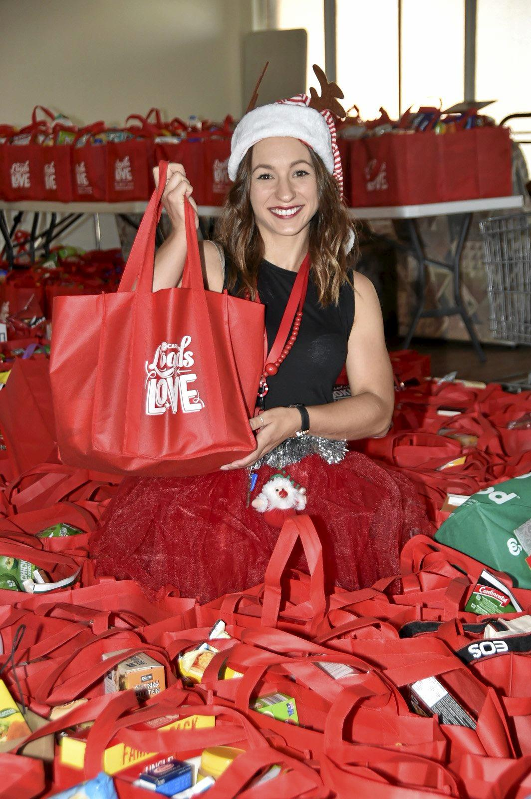 Tabina Russell from Act for Kids amongst the hundreds of groveries bags that will be handed out throughout the day. Loads of Love appeal final day. Lifeline Christmas appeal. December 2018