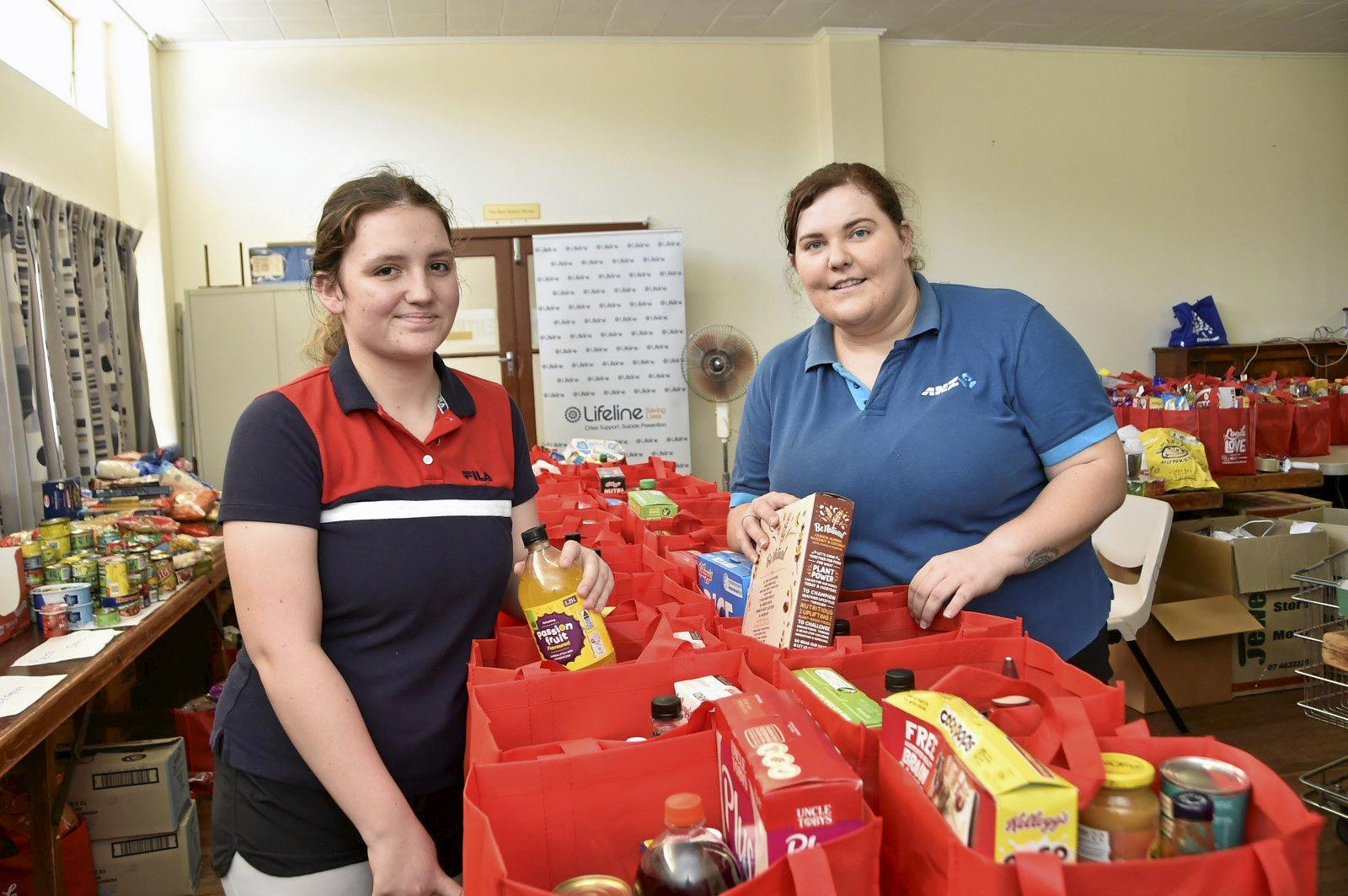 Lifeline volunteers, Darci Towning (left) and Sam Ost packing Loads of Love bags with groceries. Loads of Love appeal final day. Lifeline Christmas appeal. December 2018