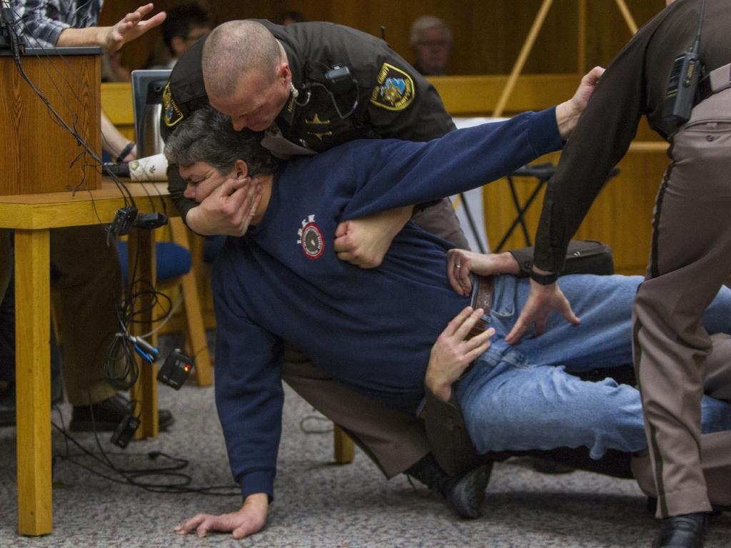 Sheriff's deputies restrain Randall Margraves, father of three victims of Larry Nassar.