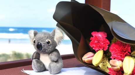 A toy bear and flowers left at the scene. Surfers Paradise beach where a 9 month old baby was found dead. Monday November 19, 2018. (AAP image, John Gass)