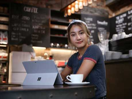 Tabiitha Ganda, who works at Lane Cove cafe The Junction, struggles to get her laptop up to speed. Picture: Sam Ruttyn