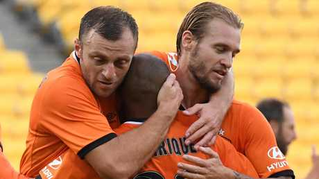 Brisbane Roar players celebrate a goal by Henrique (centre) on Saturday.