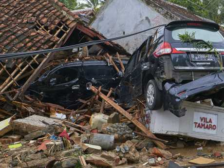 Wrecked cars lie on top of the ruins of a house destroyed by the tsunami. Picture: Getty