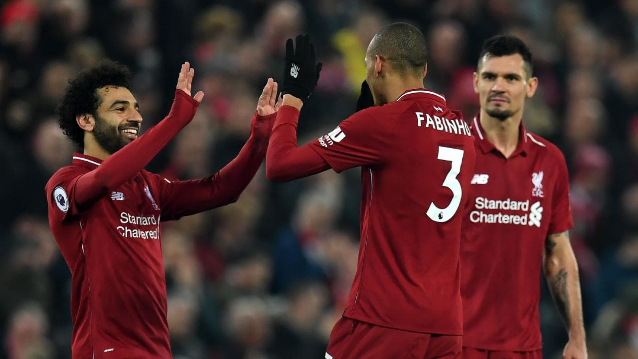 Liverpool's Brazilian midfielder Fabinho (C) celebrates with Mohamed Salah (L) and Dejan Lovren (R)