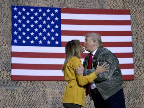 A kiss in front of the American flag. Picture: AP Photo/Andrew Harnik