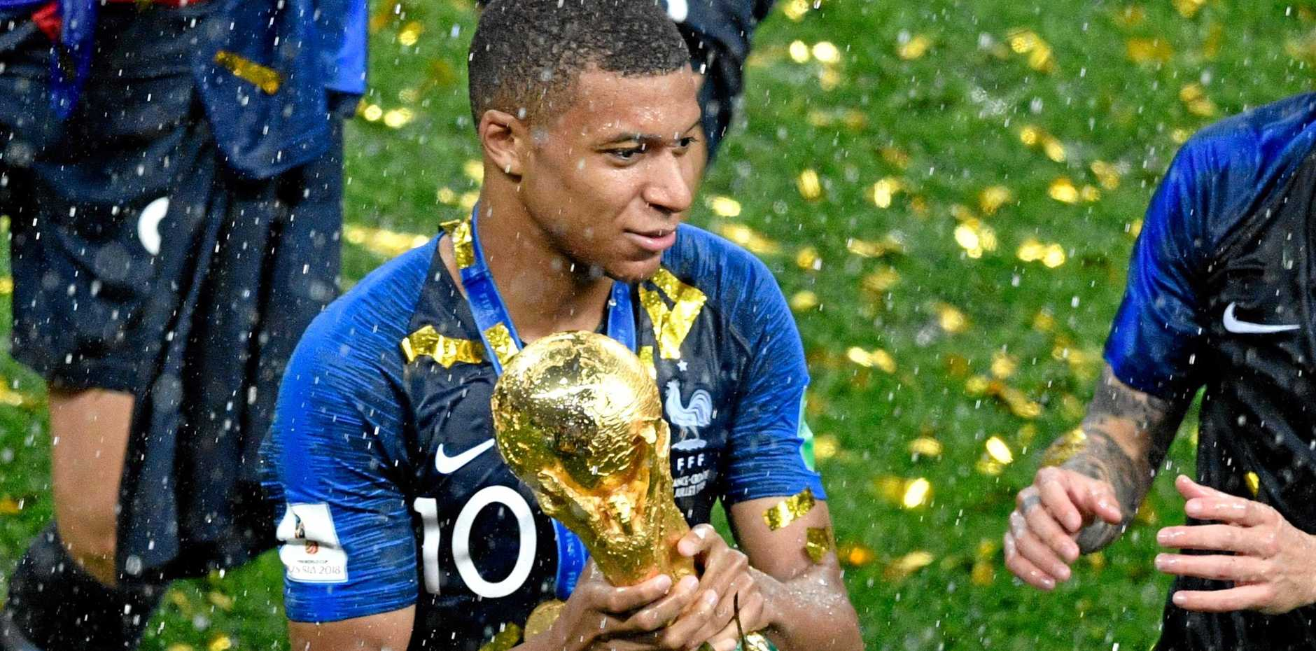 France forward Kylian Mbappe gets his hands on the World Cup trophy. Picture: Alexander Nemenov