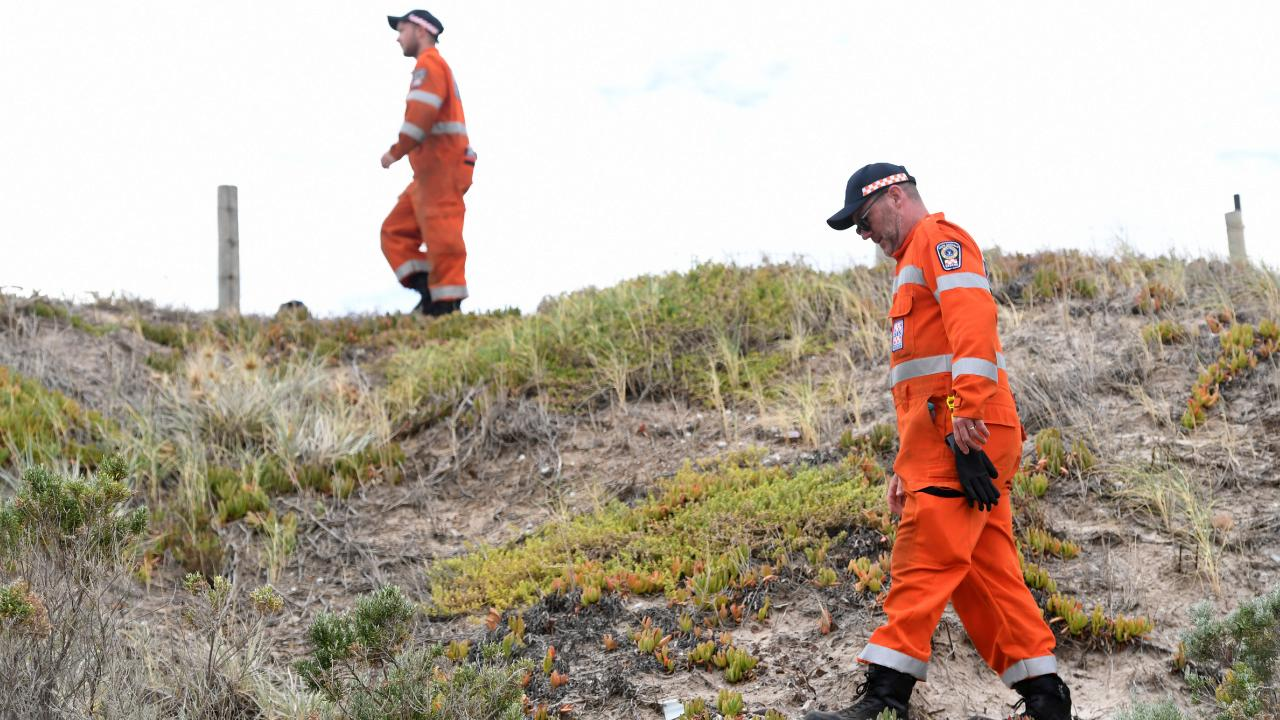 The SES searches along the sand dunes at West Beach for signs of missing man man Nischal Ghimire. Picture: AAP / Mark Brake