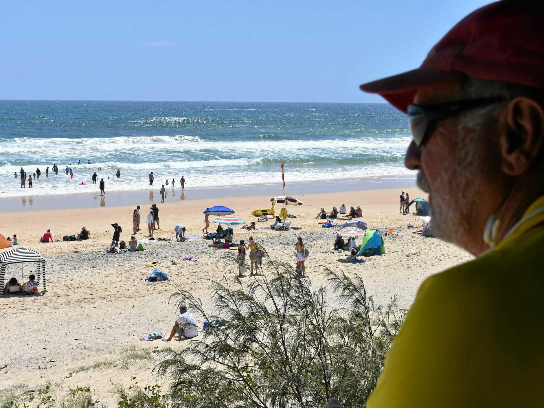 ON DUTY: Veteran Rainbow Beach lifeguard Ron Organ was keeping watch over a big crowd of bathers on Sunday.