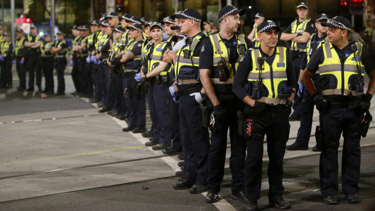 Police on the corner Flinders St and Swanston St last night. Picture: Yuri Kouzmin