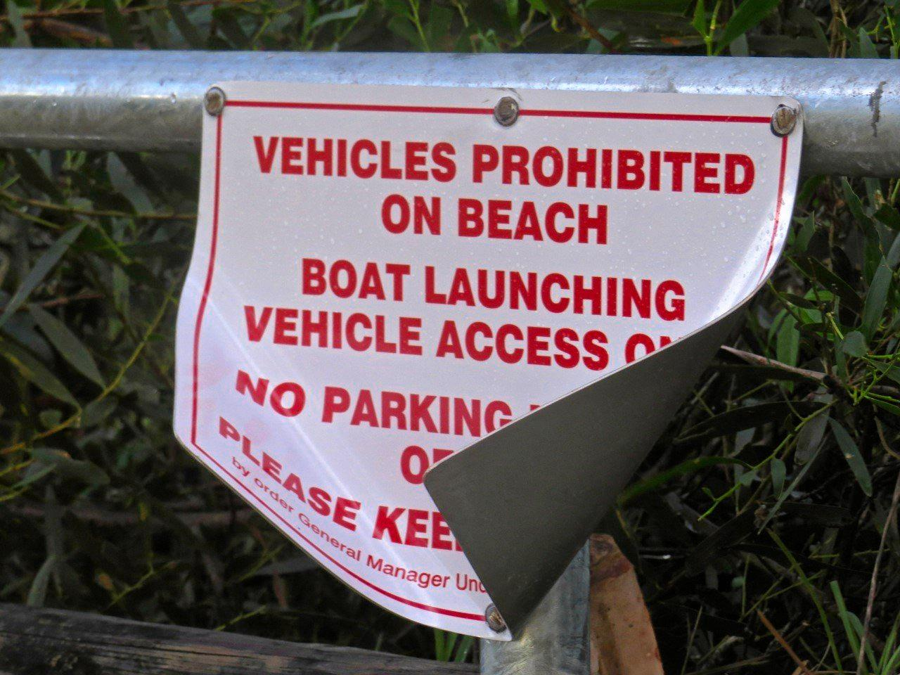 The damaged sign on the boom gate at Brooms Head beach access point.