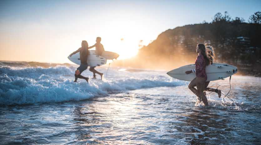 Four friends, surfers, running into the water early in the morning with surfboards in their hands. Sun is rising in back.
