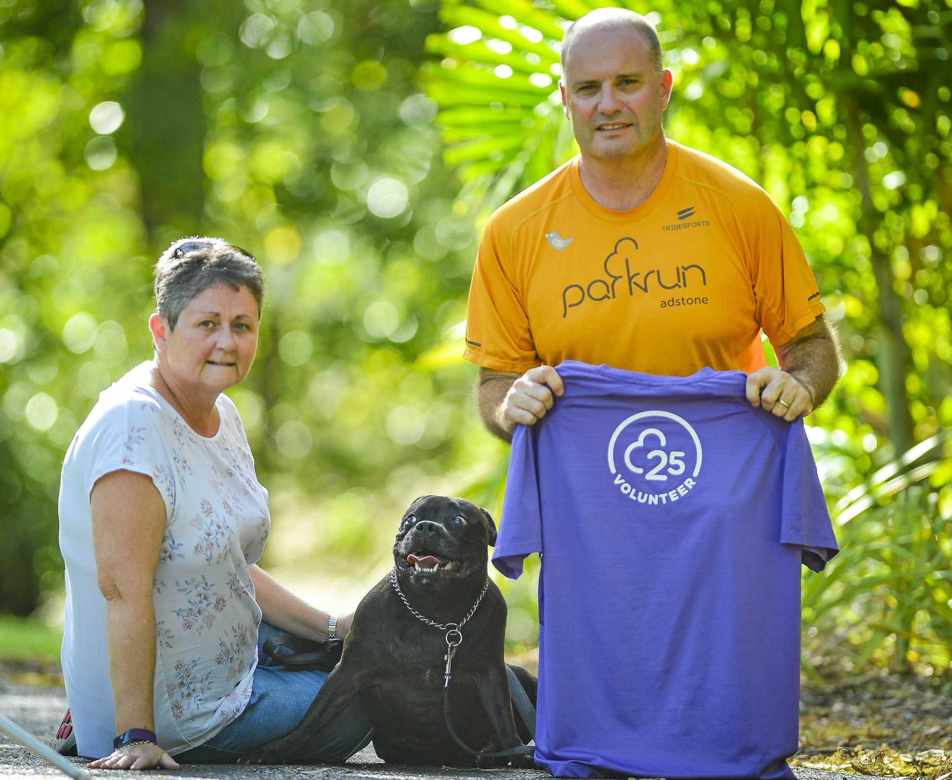 Carol Shuttleworth and dog Bo, with Steve Shuttleworth with the shirt he received after volunteering 25 times for Tannum sands Park Run.